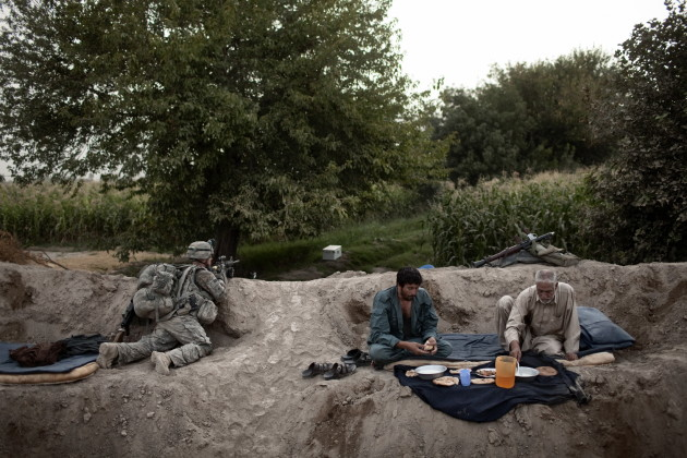 Afghan National Police broke their fast for Iftar during Ramadan while a soldier from US Military Police Battalion provided security in the Mehlajat area of Kandahar City, Afghanistan, 2010.