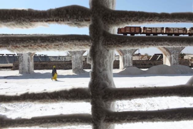 Salt factory, Rajasthan, India. Crusted salt on a window frame as a worker walks to the rail yard. © Brendan Esposito.