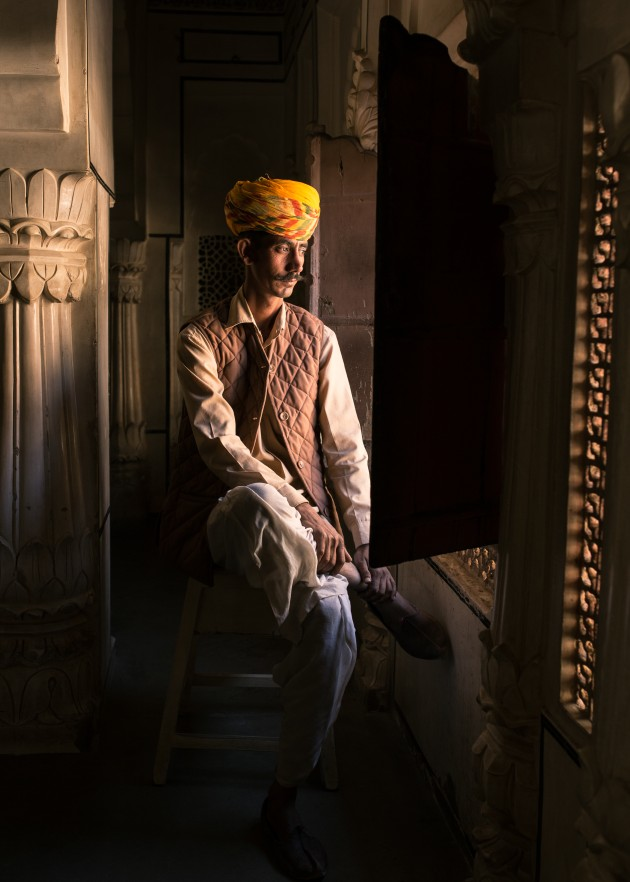 Security guard sitting by a window in Jodhpur Fort, Rajasthan, India. I shot from the hip to avoid losing the natural pose. The light illuminating his face was too good to have him turn towards me. Canon 6D, 35mm f/1.4 lens, 1/160s @ f3.5, ISO 400. Curves, contrast and white balance adjusted in Adobe Lightroom CC.
