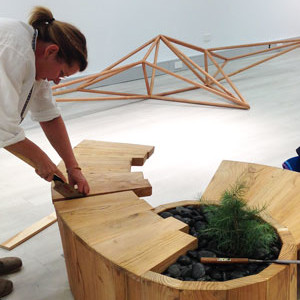 Katalin Sallai installing her 'Witness Tree from Kingston' bench made from Himalayan cedar with Matthew Harding's piece at the rear. Photo: Monica Styles