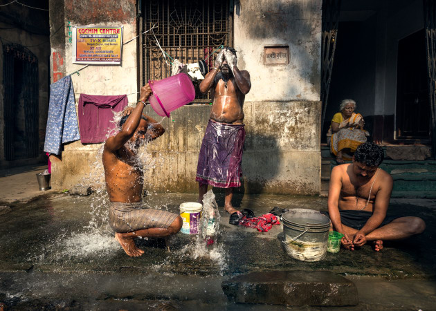 A common sight in Kolkata is people washing outside their homes on the street. I found this daily task rather photogenic. I didn't want to disturb so I shot from the hip with my camera at my waist while turning my head to the side to eliminate the possibility of being noticed. Canon, 16-35 f/2.8L II USM @ 22mm, 1/1600s @ f5.6, ISO 400. Curves, contrast, and shadow/highlight recovery in Adobe Lightroom CS5.