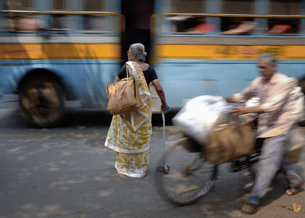 An elderly woman waits to cross a busy street in Kolkata, India. I saw the woman crossing; however freezing the action with a fast shutter lost that sense of speed as the traffic passed by. By using a slower shutter I was able to achieve a sense of motion. Fujifilm X100S, 23mm f/2 lens @ 23mm, 1/15s @ f8, ISO 200, handheld. Contrast, curves and levels adjustment, sharpening in Photoshop CC. Photo © Drew Hopper.