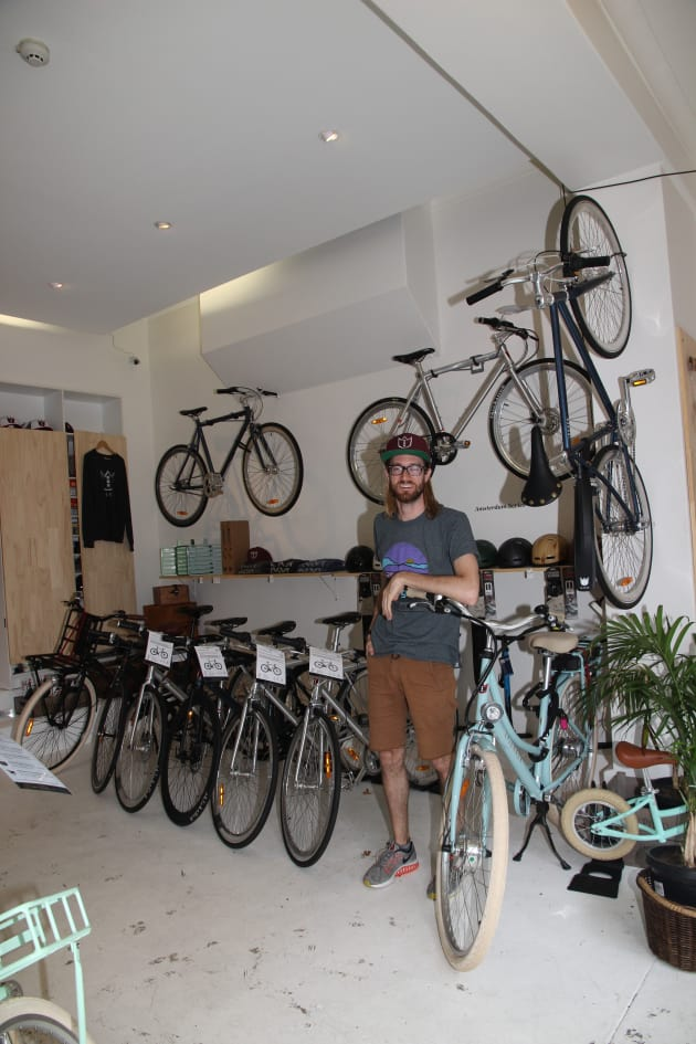 Store manager Colin Jeffery inside Lekker Bikes Sydney. The store is small with two rows of bikes on the floor and some more on the walls and outside, making perhaps two dozen in total.