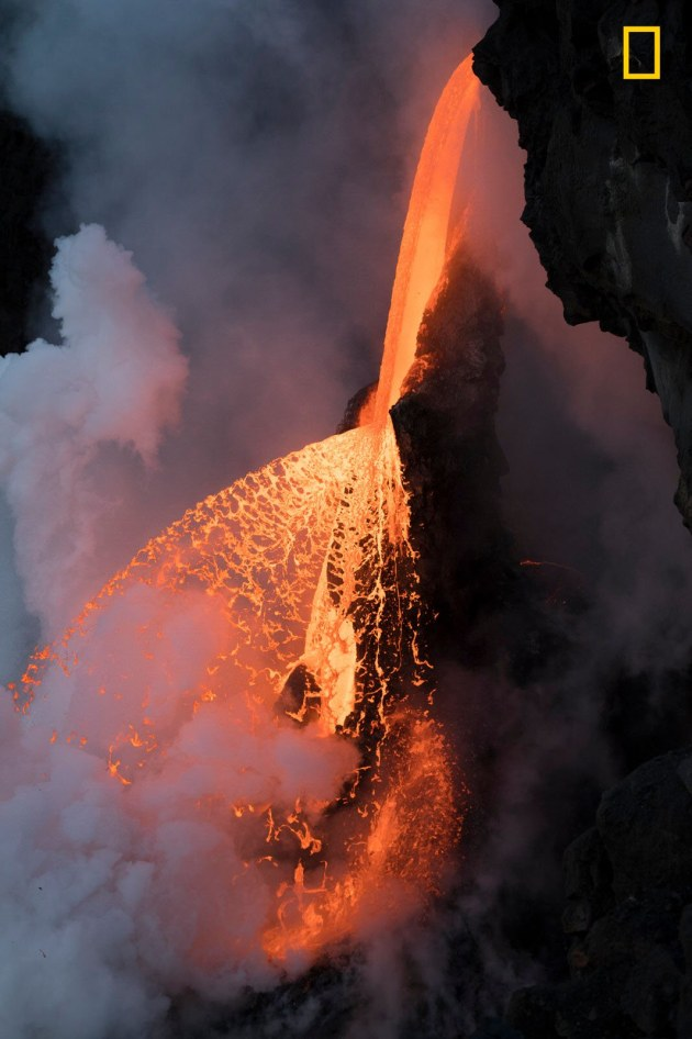 Photograph by Karim Iliya, 2017 National Geographic Nature Photographer of the Year. Shortly before twilight in Kalapana, Hawai'i, a fragment of the cooled lava tube broke away, leaving the molten rock to fan in a fiery spray for less than half an hour before returning to a steady flow.