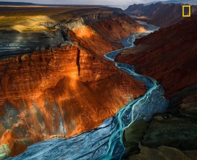 Photograph by Yuhan Liao, 2017 National Geographic Nature Photographer of the Year. Sunlight glances off mineral strata of different colors in Dushanzi Grand Canyon, China.