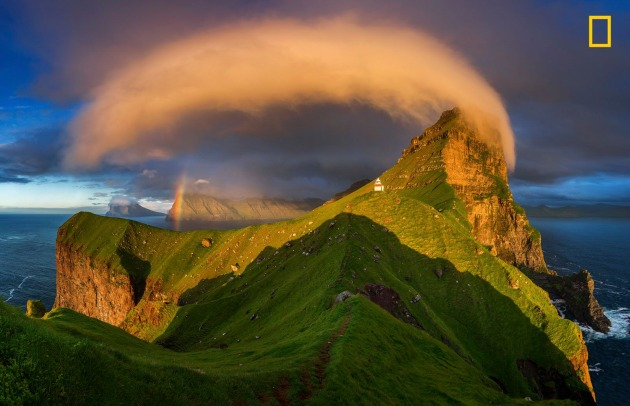 Photograph by Wojciech Kruczyński, 2017 National Geographic Nature Photographer of the Year. Sunset illuminates a lighthouse and rainbow in the Faroe Islands.