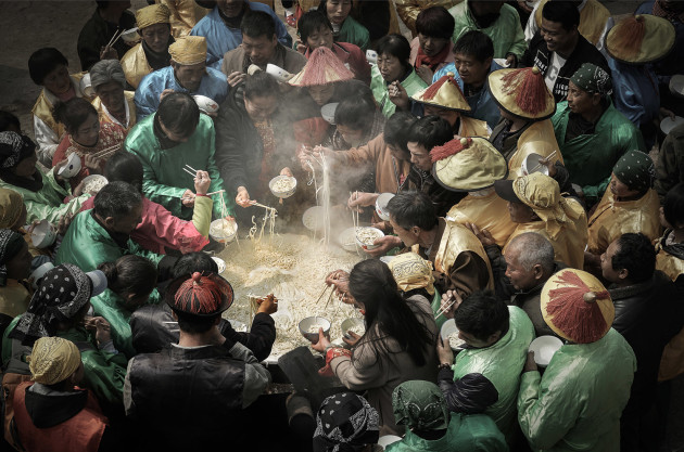 © Jianhui Liao, China. WINNER - FOOD (SINGLE IMAGE CATEGORY). Shanxi, China. A crowd gathers to eat from a huge dish of noodles.