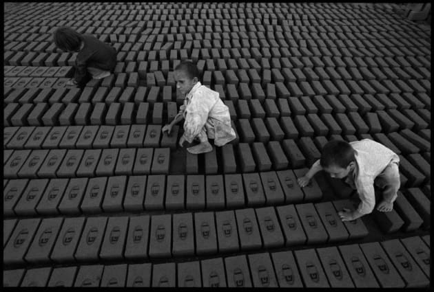 © John Stanmeyer/VII. Children tilt bricks up on their side after two days of drying at the GT Brick factory in Karkhla, Pakistan, October 2001. The children, aged 4-6, perform this labour for their father because they are lightweight and do not deform the bricks which are still somewhat soft.