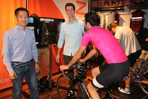 Eric Min (left) and TV presenter Matthew Keenan who was the Zwift launch host, with two of the cyclists trying their luck at winning $500 for the fastest time around a Zwift created virtual road course.
