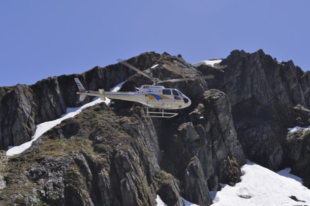 A DOC helicopter passes over Harris Saddle.