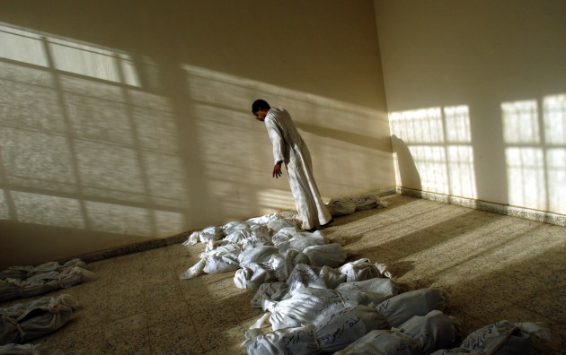 An Iraqi man leans against the wall as he walks along rows of remains of bodies discovered in a mass grave south of Bagdad, and laid out in a building in Iraq, 29 May, 2003. © Lynsey Addario.
