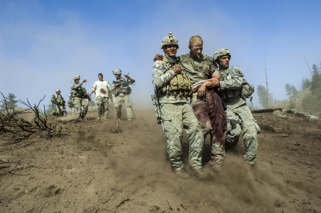 Specialist Carl Vandeberge, centre, and Sargeant Kevin Rice, behind, are assisted as they walk to a medevac helicopter minutes after they were both shot in the stomach during a Taliban ambush, which also killed one soldier. Korengal Valley, Afghanistan, 23 October, 2007. © Lynsey Addario.