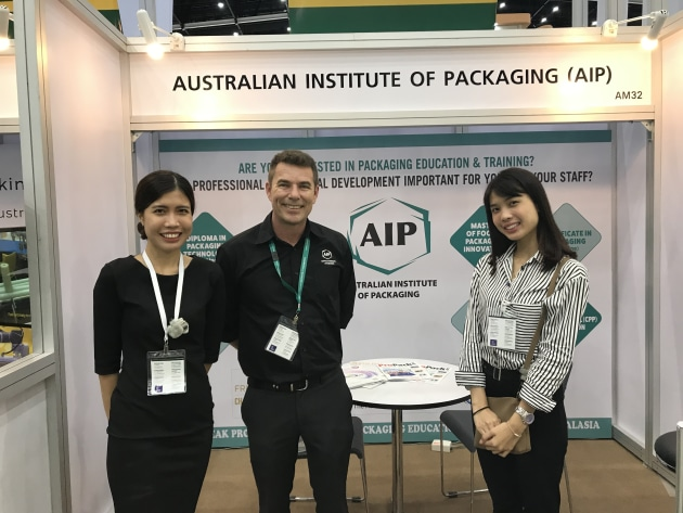 Mark Kelton  (centre) fields enquiries on the AIP stand.