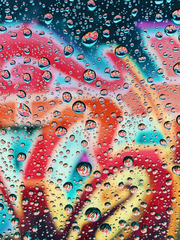 "IG: @andrewgriswold. Andrew Griswold (US), iPhone XS. Jon McCormack says: ""This image is very well thought through and executed. The background pattern holds the image together and the repeated smaller versions of that pattern in the water droplets create a lot of visual interest. The creative use of depth of field here is excellent.""  Sebastien Marineau-Mes says: ""Very unique composition and colour palette, playing to the strengths of iPhone XS. What I find most interesting is the background pattern, uniquely magnified and distorted in every one of the water droplets. I'm drawn to studying and trying to elucidate what that pattern is."""
