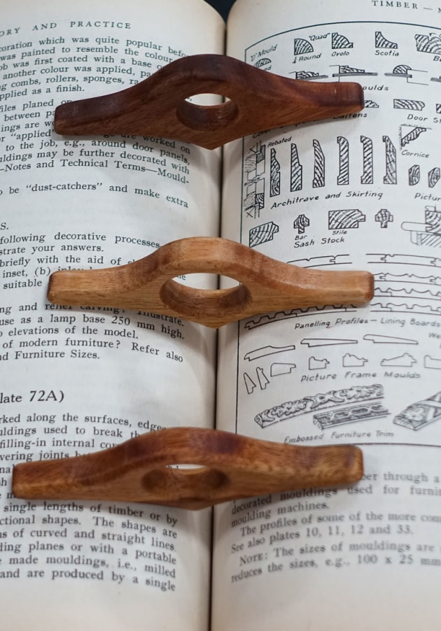 "Bevan Blackshaw, The Book Bird (Tiny Treasures), Vic ash, camphor laurel. ""My Book Birds make one handed reading easy. The pointed part engages with the spine of the book and the wings hold the pages open. The hole can be sized to fit most thumbs. I generally make these in four sizes so they fit a wide range of thumbs. Best fit is up to the first knuckle of the thumb. They came about as a way to use a regular piece of workshop scrap and small off cuts from other work thus creating a product from potential landfill."""