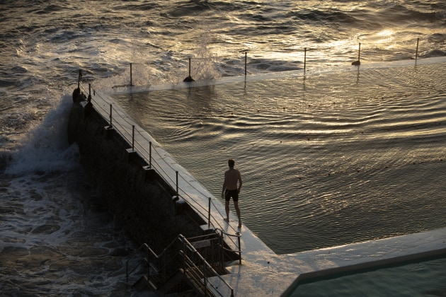 © Craig Wall. First swimmer ventures out at dawn. Bondi Icebergs ocean pool. Shot for BMW Magazine.