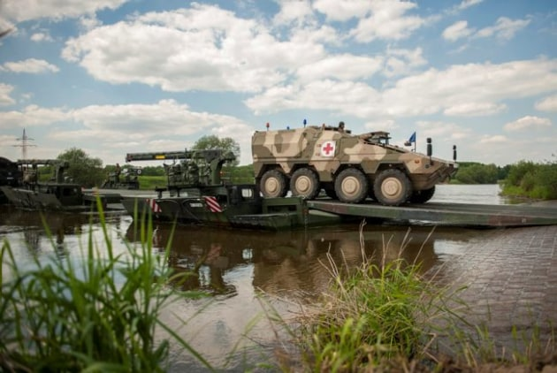 A German BOXER ambulance vehicle crossing a British temporary bridge during a joint UK/German operation.