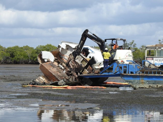 Contractors remove a derelict vessel from waters between Macleay and Garden Islands, southern Moreton Bay