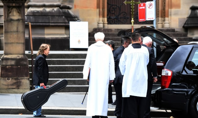 Angus Young waits to place a guitar in the hearse carrying the casket of his brother, AC/DC co-founder and guitarist Malcolm Young. The funeral was held at St Mary's Cathedral in Sydney in November 2017. © Dean Lewins