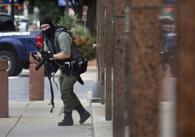 Finalist - Breaking News Photography. © Tom Fox. Armed with an AR-15 style rife, Brian Isaack Clyde attacked the Earle Cabell Federal Building and Courthouse, Monday morning, June 17, 2019 in downtown Dallas. Courthouse security returned fire. The man, wearing a mask and combat gear, was fatally shot by courthouse security while he opened fire on the rear entry. No one else was injured. Clyde ran into a parking lot across the street, collapsed and died at the scene. Here, he picks up a clip he dropped as he approached the rear of the courthouse. (June 18, 2019)