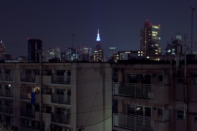 Aoyama Kitamachi Danchi. Silhouetted by the lights of the city, Aoyama Kitamachi Danchi was one of the first of its kind in Tokyo, located in the sought after shopping district of Aoyama. Redevelopment sealed its fate and the complex has been scheduled for demolition in 2019. © Cody Ellingham.