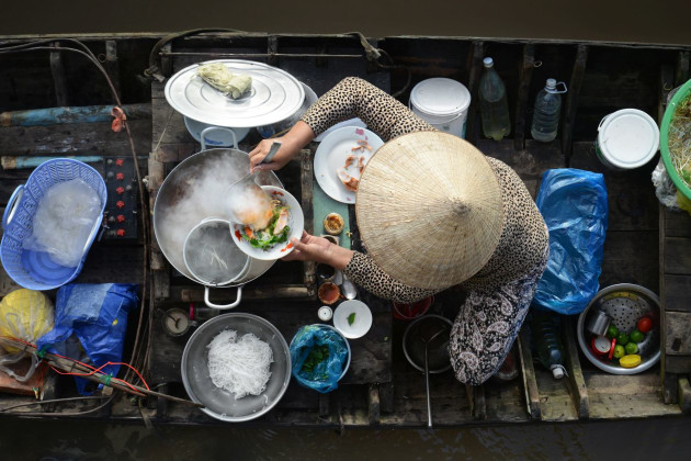 Mekong Delta breakfast, Vietnam, shot from a wooden balcony. I ordered some food at an early morning floating market in order to capture the circular shapes, especially from the lady's hat which is so iconic to Vietnam. Nikon D800, 24-85mm f/2.8-4 lens. 1/160s @ f10, ISO 400.