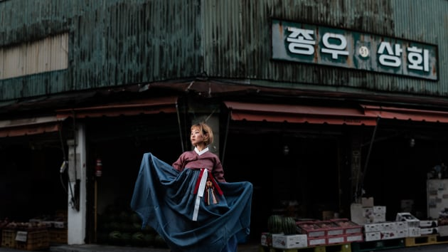 Fujifilm GFX 50S, 110mm f/2, 1/250, f/2.8, ISO 100, Godox AD200 in 1.5m umbrella to camera left, panorama stitched in Photoshop CC. Hanbok, Korea's traditional dress in a street market.