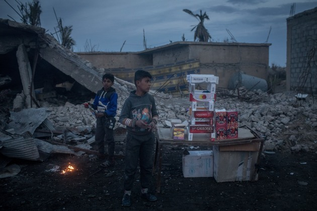 © Chris McGrath. The End of the Caliphate. BAGHOUZ, SYRIA - FEBRUARY 10: Boys sell cigarettes on the roadside in front of destroyed buildings on the outskirts of Baghouz on February 10, 2019 in Bagouz, Syria. US-led coalition airstrikes continued across Bagouz as the SDF stepped up their final campaign to oust the remaining ISIL fighters from the last village held by the extremist group.