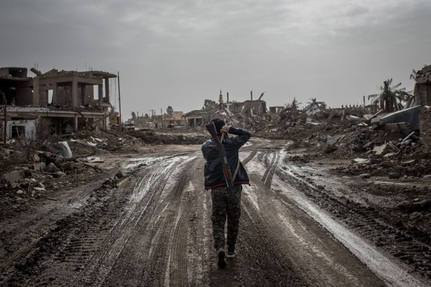 © Chris McGrath. The End of the Caliphate. AS SUSAH, SYRIA - FEBRUARY 16: An SDF fighter walks down a empty street amid destruction on February 16, 2019 in As Susah, Syria. Civilians have begun returning to some small towns close to Bagouz that were recently liberated by the US-led coalition and the Syrian Democratic Forces (SDF). Fighting continues in a small section in the west of Bagouz. SDF General Ciya announced today that ISIl fighters were holding just a 700sq meter area.