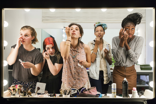 © Lauren Greenfield. High school seniors (from left) Lili, 17, Nicole, 18, Lauren, 18, Luna, 18, and Sam, 17, put on their makeup in front of a two-way mirror for the author's Beauty CULTure documentary, Los Angeles, 2011, from the Generation Wealth series 2011, archival pigment print, 67.9 x 101.6 x 3.3 (image).