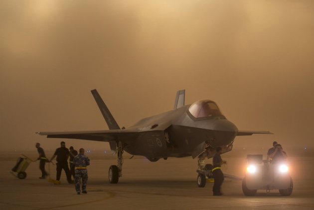 Lockheed Martin and Royal Australian Air Force maintenance personnel prepare to tow an Australian F-35A aircraft during a sudden dust storm at Luke Air Force Base, Arizona, USA. Defence