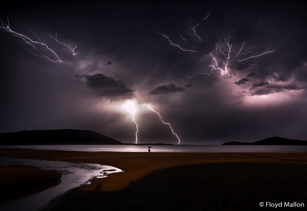 © Floyd Mallon (Age 17). WINNER, JUNIOR. This night was the most amazing display of lightning that I have ever seen, with constant flashes of lightning lasting hours. For the composition, I decided to focus on a man standing at the edge of the water with an umbrella to add a sense of scale to the image. Fingal Bay, New South Wales.