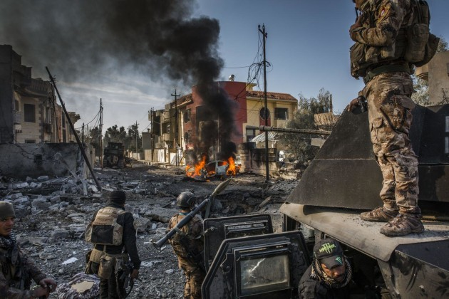 © Ivor Prickett. The Battle for Mosul. Iraqi Special Forces soldiers survey the aftermath of an attack by an ISIS suicide car bomber who managed to reach their lines in the Andalus neighborhood, one of the last areas to be liberated in eastern Mosul.