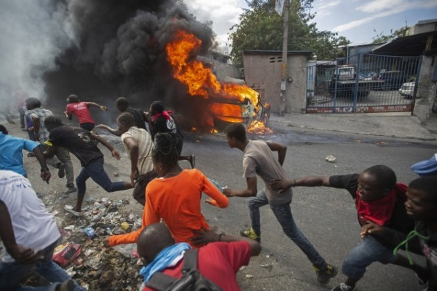 Finalist - Breaking News Photography. © Dieu Nalio Chery. Demonstrators run away from police who were shooting in their direction, as a car burns during a protest demanding the resignation of Haitian President Jovenel Moise in Port-au-Prince, Haiti, Tuesday, Feb. 12, 2019.