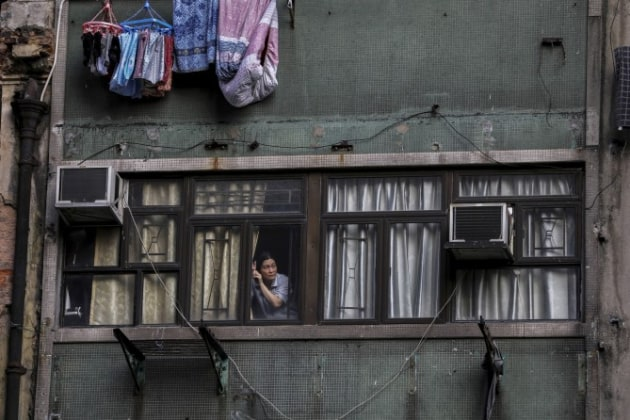 Winner - Breaking News Photography. © Ammar Awad (Photography Staff of Reuters). A woman looks out from the window of a residence as tens of thousands of demonstrators march through Hong Kong, China on October 20, 2019, demanding autonomy and for its leaders to step down weeks after the formal withdrawal of an extradition bill. The protests where triggered in February 2019 after Hong Kong's Security Bureau proposed amendments to extradition laws that would allow extraditions to countries, including mainland China, beyond the 20 states with which Hong Kong already has treaties. (Ammar Awad/December 31, 2019)