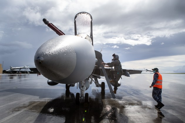 A pilot from No. 77 Squadron boards an F/A-18A Hornet A21-36 aircraft prior to an air-sea integration mission at Andersen Air Force Base.