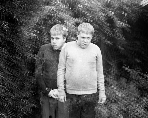 Mirror identical twins with autism 2018 Sarah Rhodes Gelatin silver print Liam and Rohan, aged eighteen, are mirror identical twins with severe autism. One is left-handed, the other right-handed. One is high functioning; the other is lower functioning. They are both socially isolated, but because they are twins they have each other. I made this image as a double exposure to represent the boys' identicalness, but also to offer an insight into their minds, particularly their anxiety. The background of the image seeps through, suggesting these two boys could be the same person – different sides of the one self, one wearing black, the other wearing white.