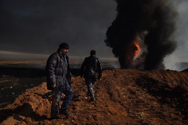 Iraqi forces guard one of the oil wells yet to be extinguished in the Qayyarah oil fields. As a parting shot, retreating ISIS fighters set 22 oil wells on fire filling the air with toxic fumes, and laid the surrounding areas with IEDs and land mines. February, 2017. © Kate Geraghty.