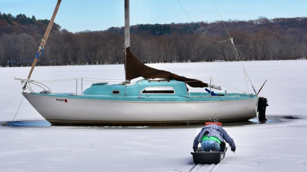 """I don't think I can move it now,"" said Mike Olson, of his 26-foot white-and-blue fiberglass 1977 Pearson sailboat which is frozen in the St. Croix River north of Stillwater. He uses ice picks while he kneels in a sport sled to get to the boat to check for damage Friday, Nov. 15, 2019. (Jean Pieri / Pioneer Press)"