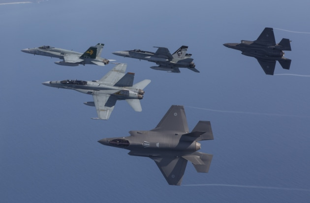 F-35A Joint Strike Fighters fly in formation with an F/A18 Hornets.