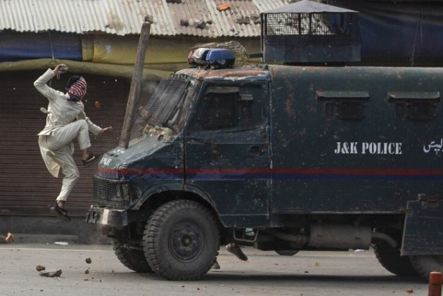 Winner - Feature Photography. © Dar Yasin. A masked Kashmiri protester jumps on the bonnet of an armored vehicle of Indian police as he throws stones at it during a protest in Srinagar, Indian controlled Kashmir, Friday, May 31, 2019.