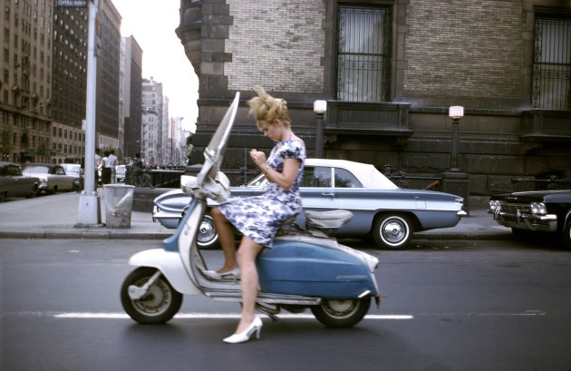 "Joel Meyerowitz Aperture New York City, 1965. ""A girl on a Vespa on her way to 'who knows where,' when the light stopped her at the 72nd street crossing near the Dakota, where John Lennon would one day cross paths with his fate. She takes this moment to finesse a fingernail before she resumes her downtown journey, while I, stopping at the same crossing, but on foot, leap into the street to capture this vision of a dream girl before time takes her on her way."" – Joel Meyerowitz"