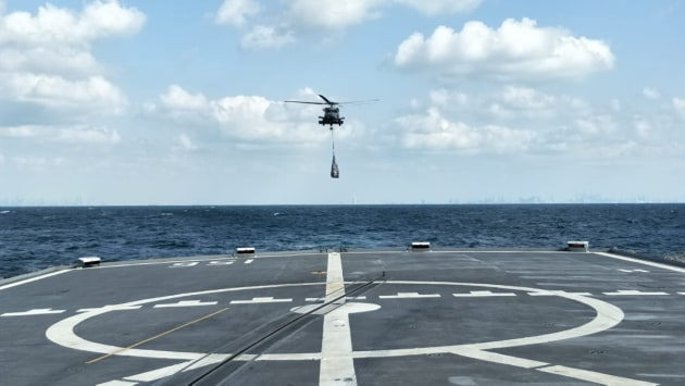 HMAS Toowoomba's embarked MH-60R helicopter approaches the flight deck to deliver priority stores and mail.