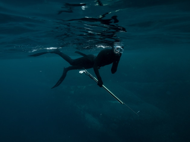 © Michaela Skovranova. Emma Shearman preparing to dip underwater while spearfishing. From a story for The New York Times.