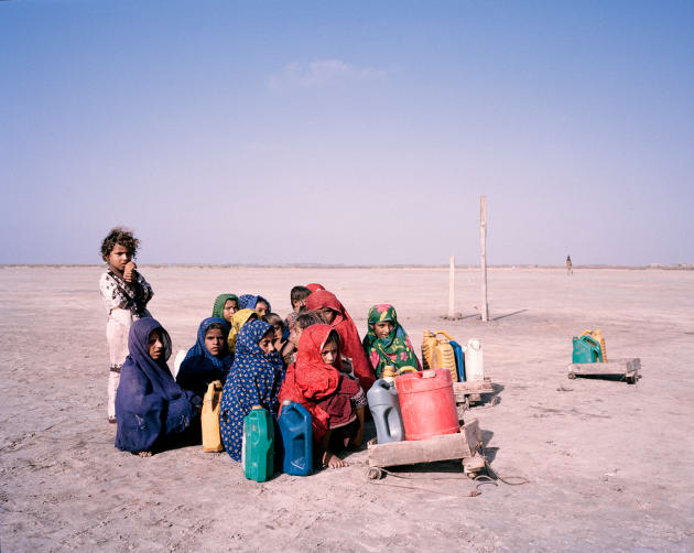Khado Muhammad Jut, Sindh, Pakistan, 2013. Children pause during their journey to collect water, huddling together against the wind in southern Sindh. Floods gripped the country in 2010 and 2011, leaving behind only barren land. Agriculture in the region was devastated.
