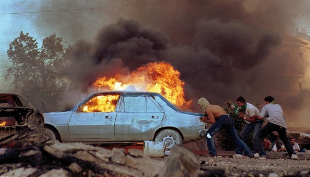 © Ami Vitale. Palestinians burn cars as protests flared again near the West Bank town of Ramallah, 11 October, 2000.