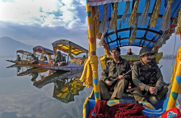 © Ami Vitale. Indian Border Security Force Officers patrol the picturesque Dal Lake, in the summer capital of Srinagar, in the Indian-held state of Kashmir, 19 February, 2002.