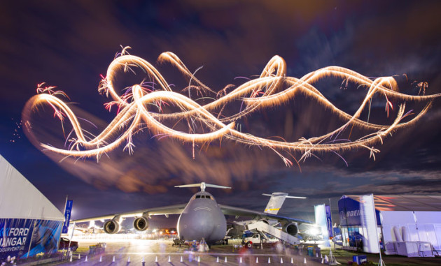 Night aerobatics paint the night sky above a US Air Force C5 Galaxy at Airventure 2019. (Chris Miller / Experimental Aircraft Association)