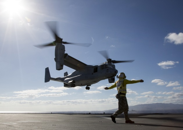Leading Seaman Aviation Support Jamie Kennedy signals to a US Marine V-22 Osprey.