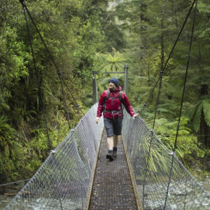 Walking one of several swing bridges along the Hollyford Track.